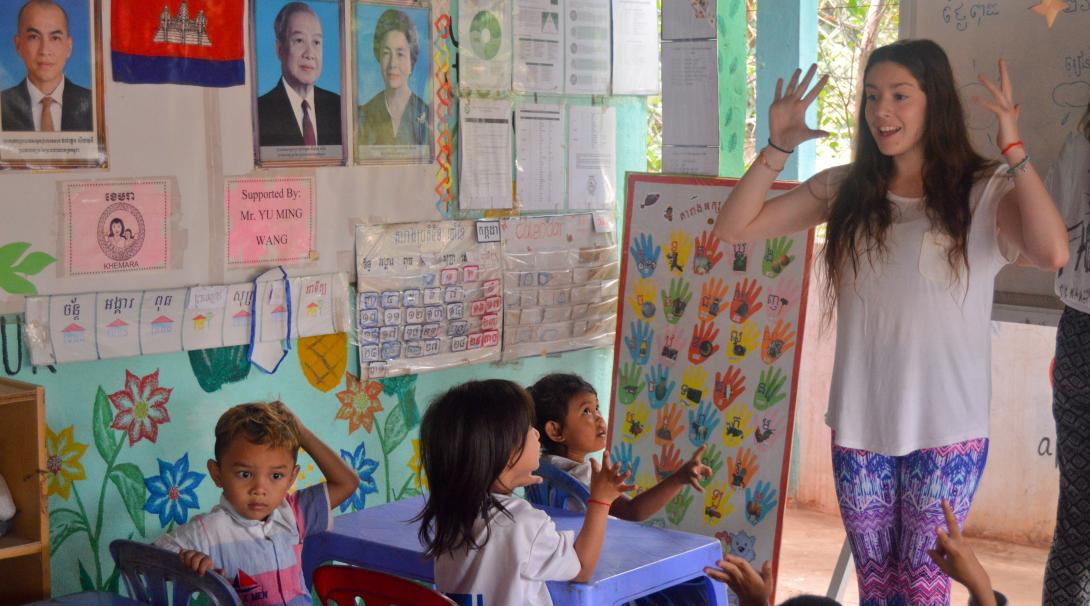 A High School Special Volunteer is teaching English words to the local children at the care & community placement during her volunteering trip in Cambodia.